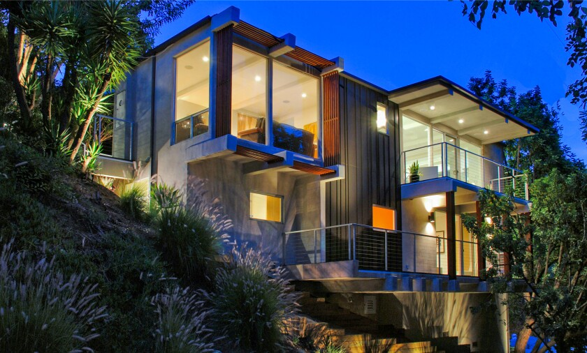 The secluded two-story home takes in canyon views from a balcony with a sauna and from an outdoor lounge with a waterfall.