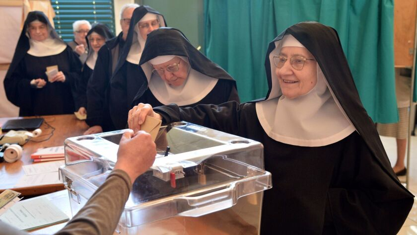 A Benedictine sister of the Sainte-Cecile Abbey casts her ballot at a polling station in Solesmes, n