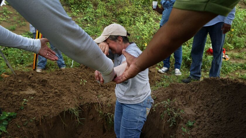 Rosalia Castro, 61, whose son disappeared in 2011, is overcome with emotion while helping to excavate a clandestine grave in Mexico's Veracruz state.