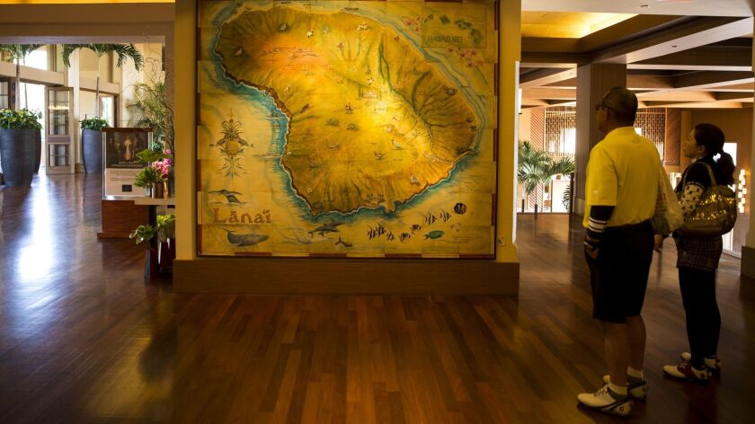 LANAI CITY, HI - APRIL 03: Visitors look at a map of the the Hawaiian island of Lanai in the lobby o