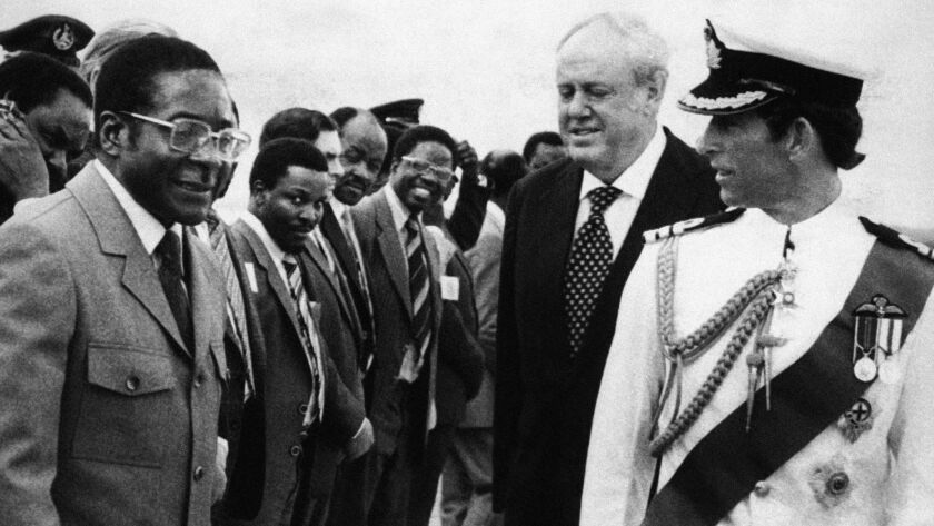 FILE - In this April 16, 1980, file photo, Britain's Prince Charles, right, speaks with Zimbabwe's P
