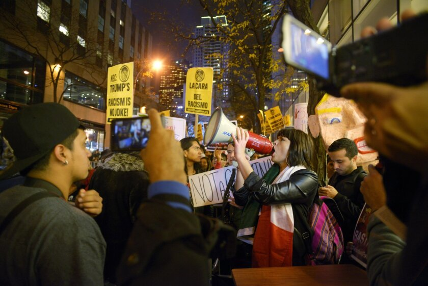 "Karina Garcia, of the ANSWER Coalition, uses a megaphone to lead demonstrators in a chant during a protest against Republican presidential candidate Donald Trump's hosting ""Saturday Night Live"" in New York, Saturday, Nov. 7, 2015. Despite a 40-year history of lampooning politicians while inviting s"
