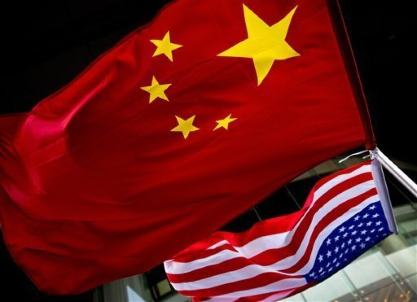 In this Nov. 7, 2012 photo, U.S. and Chinese national flags are hung outside a hotel during the U.S. Presidential election event, organized by the U.S. embassy in Beijing. As public evidence mounts that the Chinese military is responsible for stealing massive amounts of U.S. government data and cor