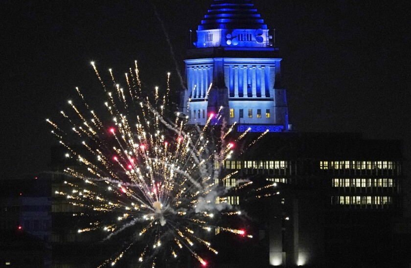 FILE - In this Oct. 27, 2020, file photo, Los Angeles City Hall is illuminated with dark blue lights as Dodgers fans celebrate with fireworks on Sunset Boulevard after watching the broadcast of Game 6 of the baseball World Series in Los Angeles. A Southern California official is seeking federal help in stopping an influx of illegal fireworks that has fueled use of skyrockets and firecrackers well beyond July 4 and led to the deadly explosion of a cache in the middle of a neighborhood this year. (AP Photo/Damian Dovarganes, File)