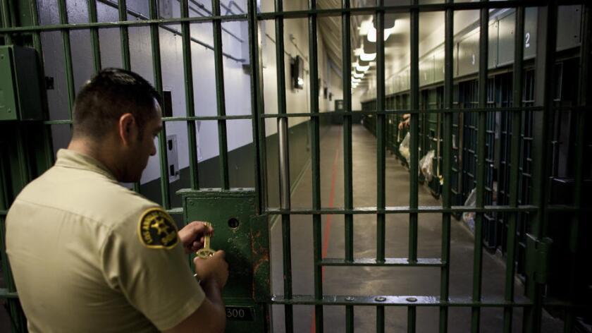 Un agente del sheriff del condado de L.A. se prepara para desbloquear una puerta de seguridad en una celda de la Cárcel Central de Hombres del Condado de L.A., en 2011 (Los Angeles Times).
