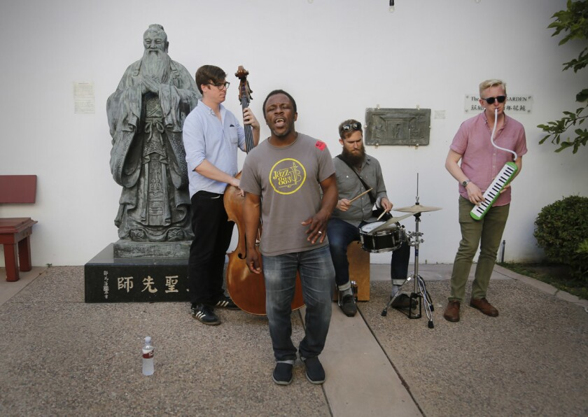 The Leonard Patton Group, with Leonard Patton on vocals, bassist Mackenzie Leighton, drummer Matt Smith, and keyboardist Ed Kornhauser, attempting to set the Guinness World Records for live music by performing at 70 San Diego County locations in just 24 hours, starting at 10am on May 2, performs in the garden at the San Diego Chinese Historical Museum, the 15th stop on their 70 venue attempt. (Howard Lipin/San Diego Union-Tribune)