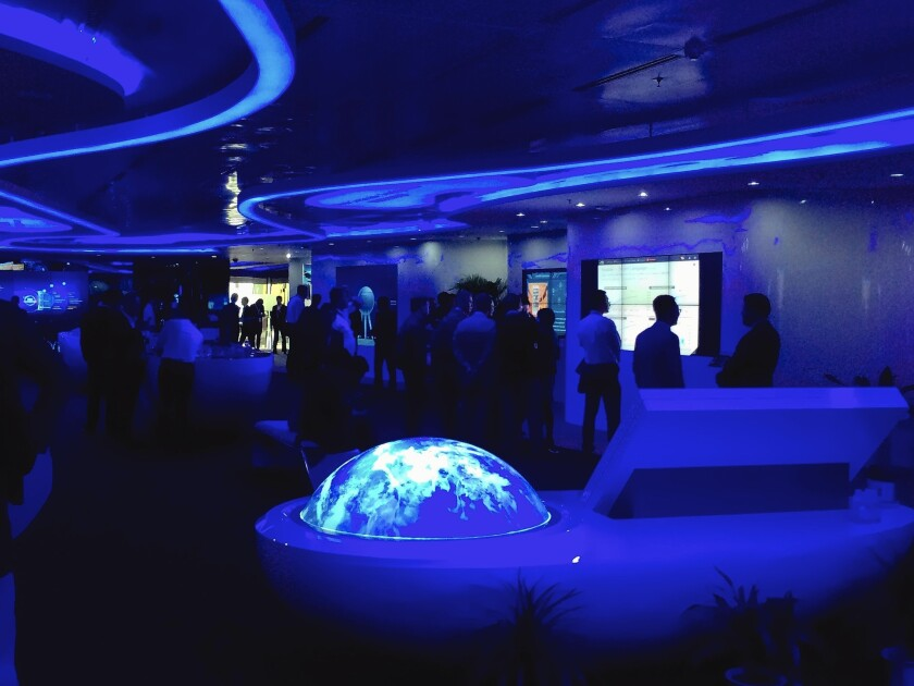 Potential buyers wander among display tables bathed in a ghostly blue light at Huawei's Global Mobile Broadband Forum in Shanghai last month.