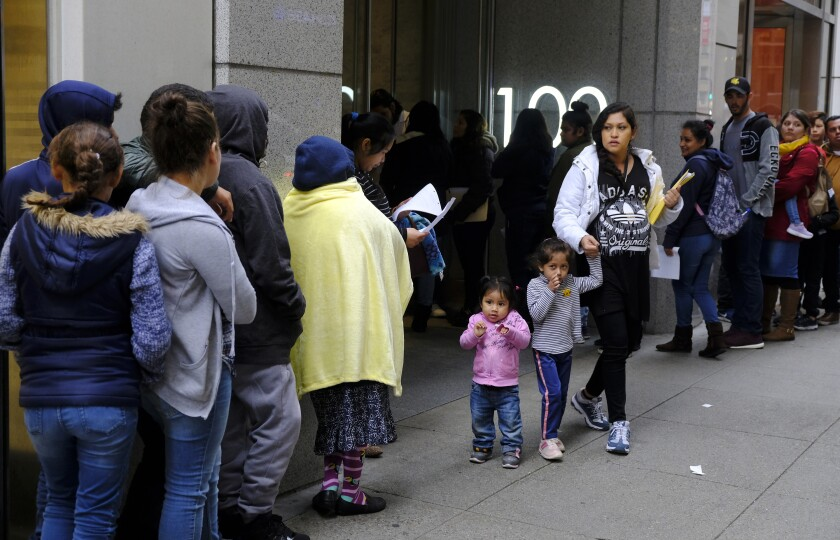 "File - In this Jan. 31, 2019, file photo, hundreds of people overflow onto the sidewalk in a line snaking around the block outside a U.S. immigration office with numerous courtrooms in San Francisco. Federal judges are being asked to block a new Trump administration policy scheduled to take effect next week that would deny legal permanent residency to many immigrants over the use of public benefits. Almost a dozen lawsuits have been filed from New York to California to prevent the ""public charge"" rule from taking effect on Oct. 15. Judges have indicated a willingness to issue rulings before the scheduled start date. (AP Photo/Eric Risberg, File)"