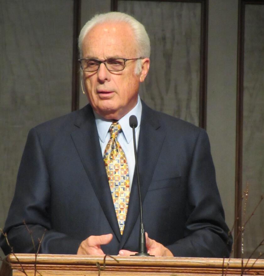 Pastor John MacArthurn stands behind a lectern