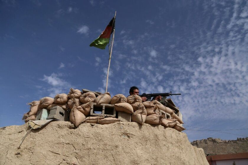 An Afghan keeps watch at a checkpoint on Highway One in Ghazni province in October.