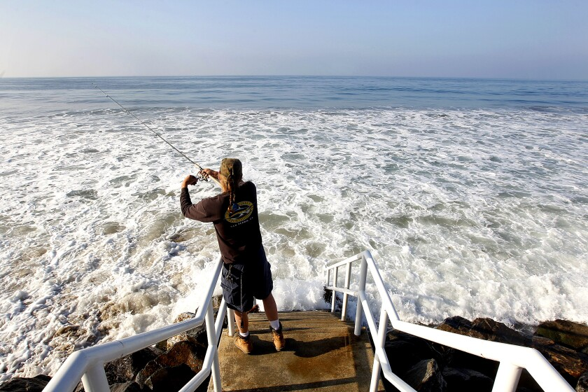 A man fishes during high tide in Malibu