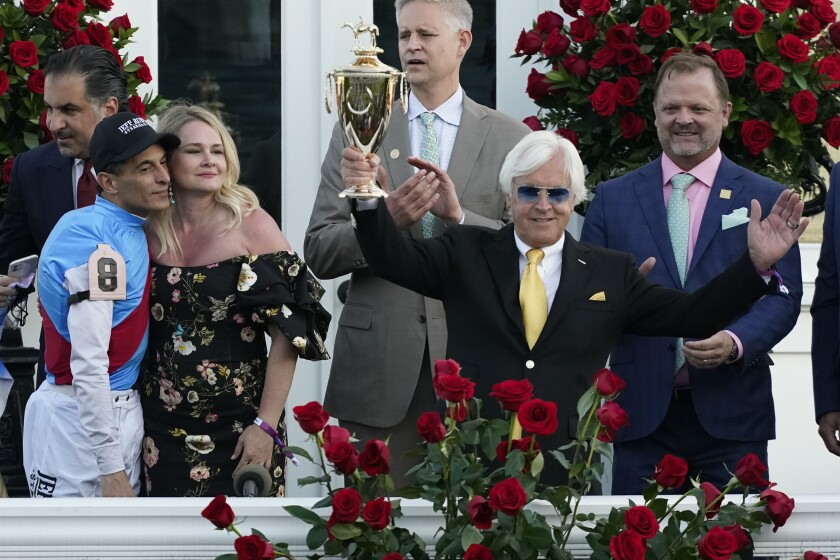 FILE - In this May 1, 2021, file photo, jockey John Velazquez, front left, stands with Jill Baffert as they watch as Jill's husband, trainer Bob Baffert, front right, holds up the winner's trophy after their victory with Medina Spirit in the 147th running of the Kentucky Derby at Churchill Downs in Louisville, Ky. A 3-year-old colt co-owned by Jill Baffert ran under the name of another Hall of Fame trainer on Saturday, July 10, 2021, when it finished fourth in the $1 million Belmont Derby Invitational at Belmont Park, where Bob Baffert has been suspended and is suing to regain access. (AP Photo/Jeff Roberson, File)