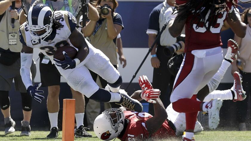 Rams running back Todd Gurley scores the first of his three touchdowns against the Cardinals on Sunday at the Coliseum in Los Angeles.