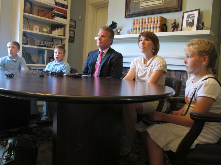 """The wife and children of Jeffrey Edward Fowle sit with their attorney, Tim Tepe, center, during a news conference at Tepe's office in Lebanon, Ohio. Fowle has been charged with """"anti-state"""" crimes in North Korea. Fowle's family apologized Tuesday to the communist country and pleaded for its government to show him mercy, saying in a statement they're """"desperate for his release and return home."""" From left are: Fowle's sons, Alex, 13, and Chris, 11; wife Tatyana, 40, and daughter Stephanie, 9. (AP Photo/Amanda Lee Myers)"""