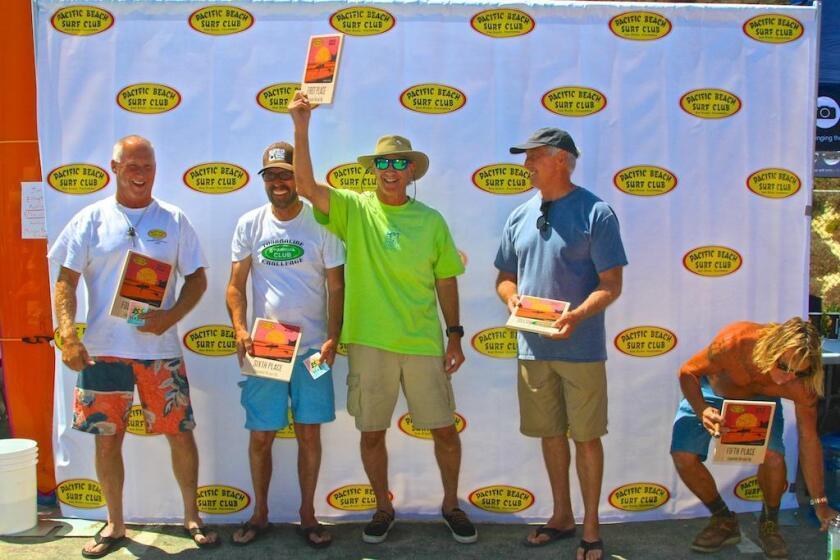 Ron Greene, president of PB Surf Club and event organizer, shows off his first place trophy as winner of the Men's Legends group.