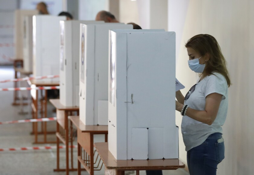 People read their ballot papers at a polling station during a parliamentary election in Yerevan, Armenia, Sunday, June 20, 2021. Armenians are voting in a national election after months of tensions over last year's defeat in fighting against Azerbaijan over the separatist region of Nagorno-Karabakh. (AP Photo/Sergei Grits)