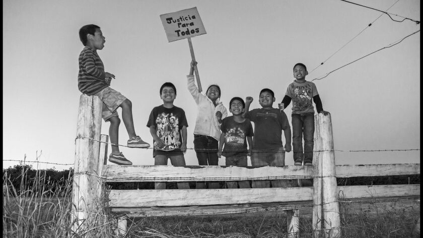 "A photograph from the book ""In the Fields of the North."" Outside the labor camp, the children of str"