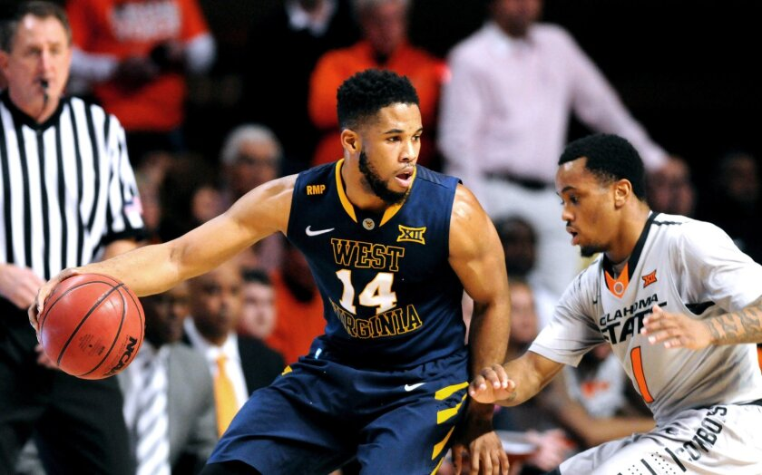 West Virginia guard Gary Browne (14) watches Oklahoma State guard Tyree Griffin while bringing the ball down court during the first half of an NCAA college basketball game in Stillwater, Okla., Saturday, Feb. 21, 2015. (AP Photo/Brody Schmidt)