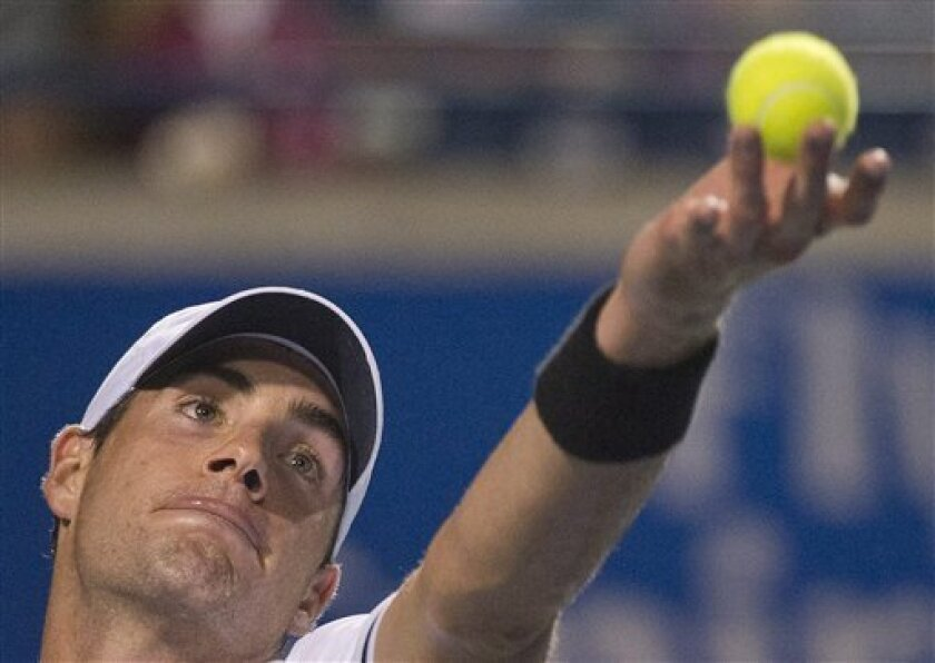 John Isner of the United States serves the ball against Milos Raonic of Canada during Rogers Cup quarter-final tennis action in Toronto on Friday, Aug. 10, 2012. (AP Photo/The Canadian Press, Nathan Denette)