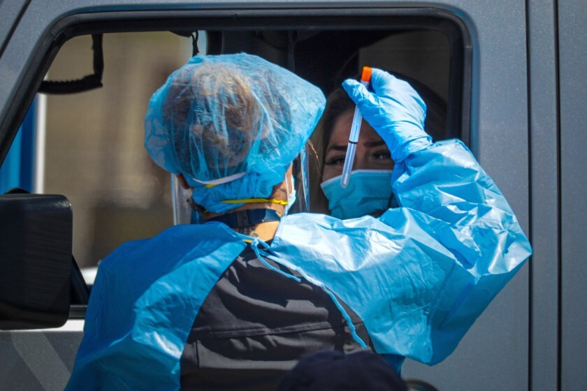A San Bernardino County healthcare worker collects a sample at a drive-through coronavirus testing site in Victorville.