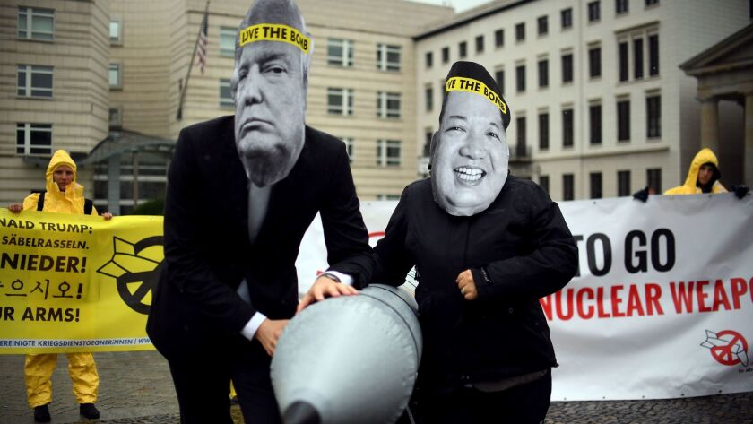 Members of the International Campaign to Abolish Nuclear Weapons, wearing masks of President Trump and North Korean leader Kim Jong Un, protest the U.S.-North Korea conflict at the U.S. Embassy in Berlin.