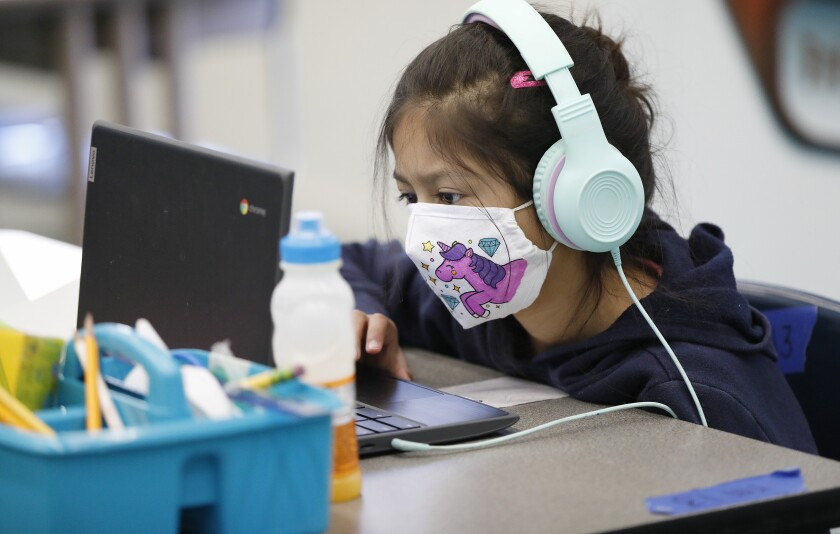 A 2nd-grader wears a mask as she works at a computer.