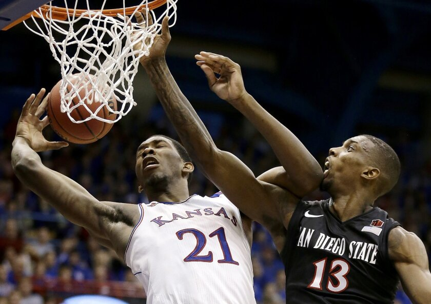 Kansas' Joel Embiid (21) and San Diego State's Winston Shepard (13) battle for a rebound during the second half.