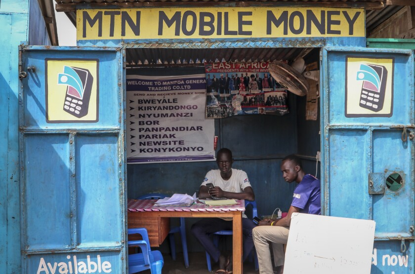 In this photo taken Tuesday, Sept. 10, 2019, a man sits in his mobile money kiosk which specializes in sending money from South Sudan to Uganda, in the capital Juba, South Sudan. South Sudan has launched mobile money, the ability to send and receive funds by phone, in an attempt to boost the economy after a five-year civil war killed almost 400,000 people. (AP Photo/Sam Mednick)