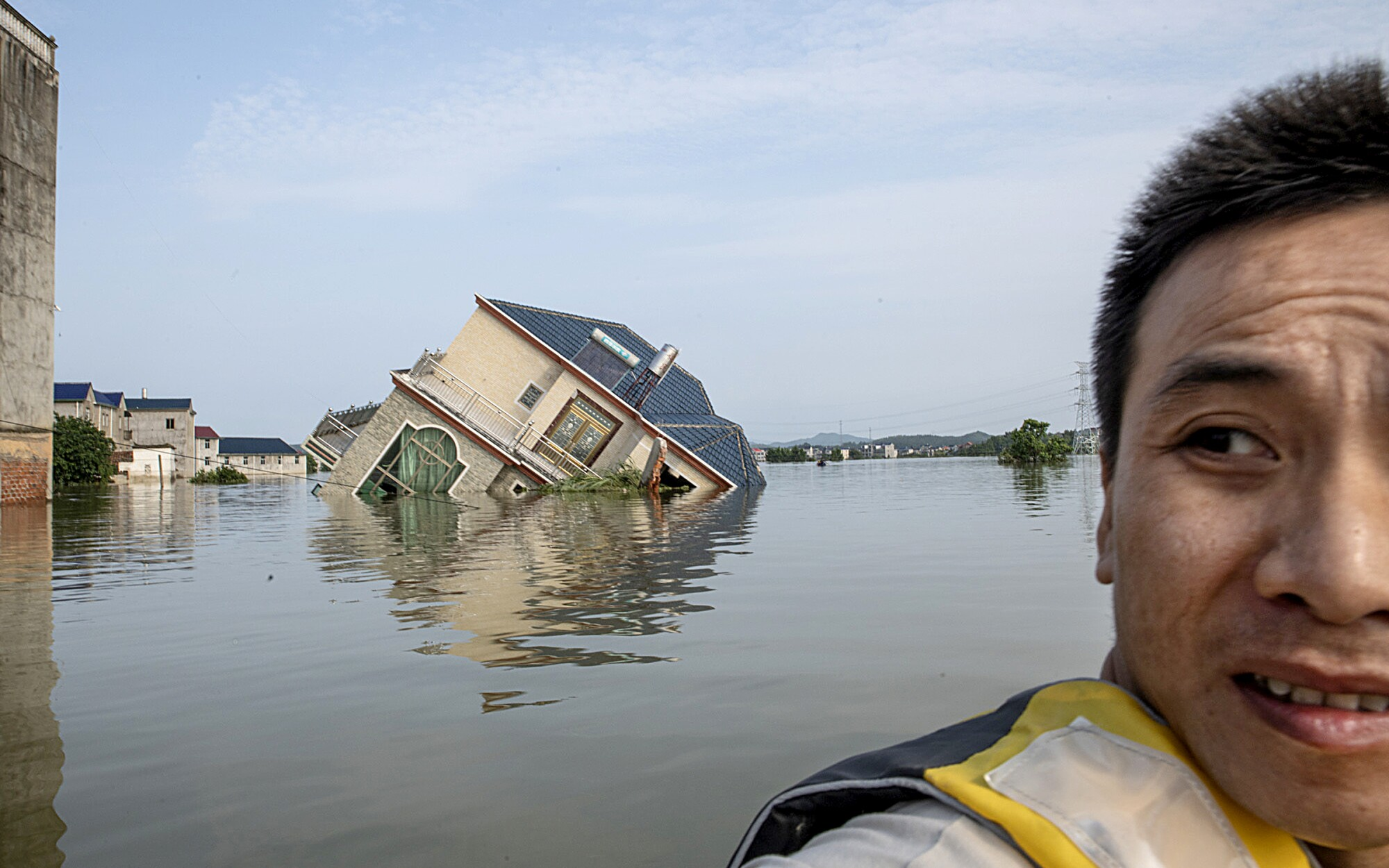 Gao, a local resident, sits on a rescue boat near a house that fell into the river in Poyang county.