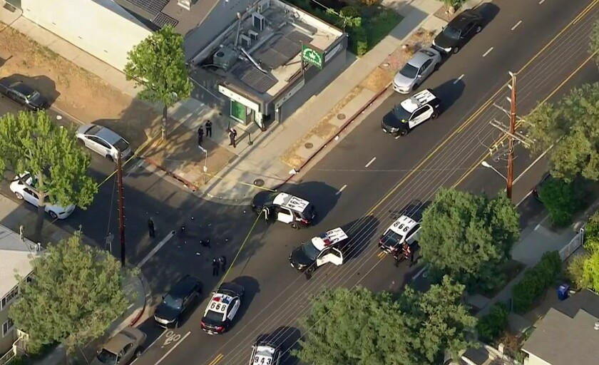 An aerial view shows several police cars in the street