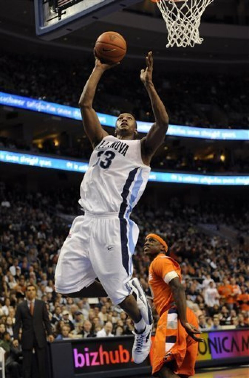 Villanova's Dante Cunningham soars to the basket past Syrcuse's Jonny Flynn during the second half of an NCAA college men's basketball game at the Wachovia Center in Philadelphia, Saturday, Feb. 07, 2009. Villanova won 102-85. (AP Photo/Michael Perez)