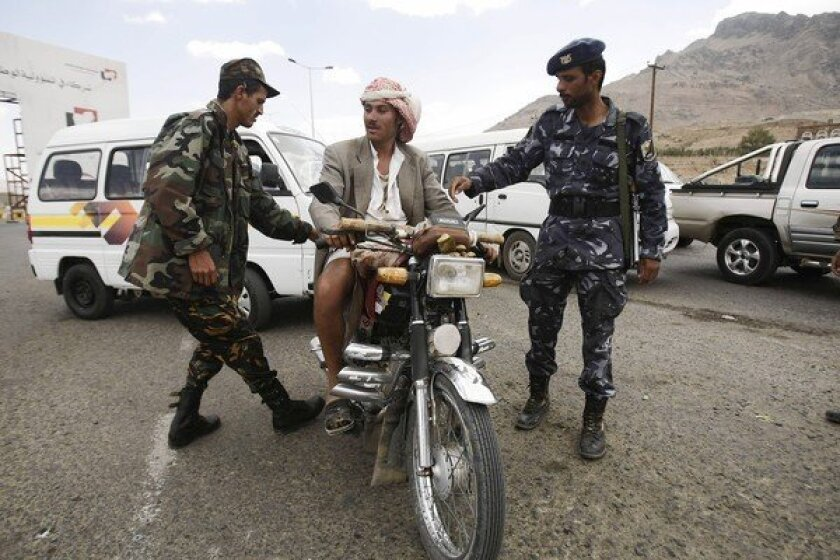 Yemeni soldiers stop a motorcyclist at a checkpoint in Sana, the capital. Security was stepped up after the Oct. 6 killing of a German Embassy guard and the kidnapping of a UNICEF employee.