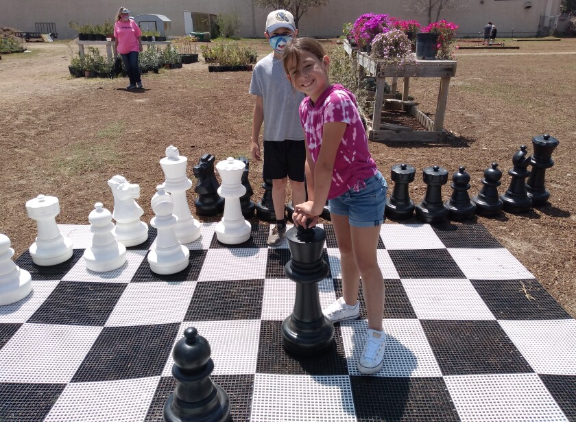 Ramona resident Violet Ilic, 9, and her friend Wyatt Songer, 8, play a game of oversized chess at Generations JADE Garden.