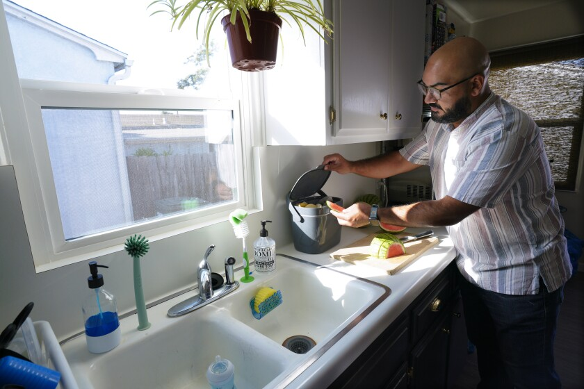 Victor Sanchez places his food waste in a special countertop food container at his home in National City on Thursday.