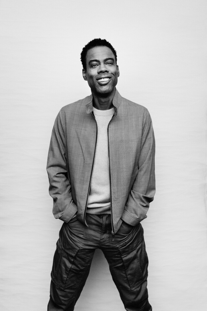 A black and white photo of Chris Rock, wearing a jacket, T-shirt and jeans and standing with his hands in his pockets.