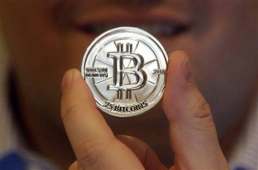 In this April 3, 2013 photo, Mike Caldwell, a 35-year-old software engineer, holds a 25 Bitcoin token at his shop in Sandy, Utah. Caldwell mints physical versions of bitcoins, cranking out homemade tokens with codes protected by tamper-proof holographic seals, a retro-futuristic kind of prepaid cas