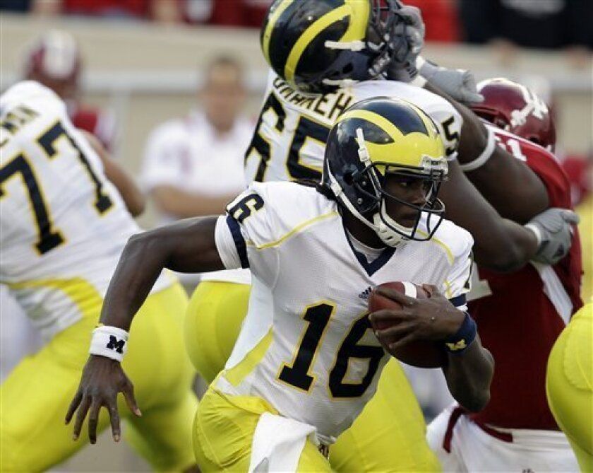 FILE - In this Oct. 2, 2010, file photo, Michigan quarterback Denard Robinson (16) runs the ball agaisnt Indiana during an NCAA college football game against in Bloomington, Ind. Michigan State withstood a Notre Dame onslaught and contained Wisconsin's running game. Now the Spartans try to stop Denard Robinson, perhaps the nation's most electrifying offensive talent. (AP Photo/Darron Cummings, File)