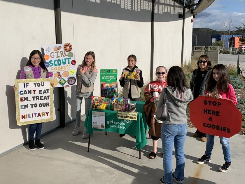 Girl Scouts (l-r) Sydney Tsai, Ressa Bader, Torrey Soloria, Kallie Schaffer, and Brooke Koliander greet a prospective cookie customer.