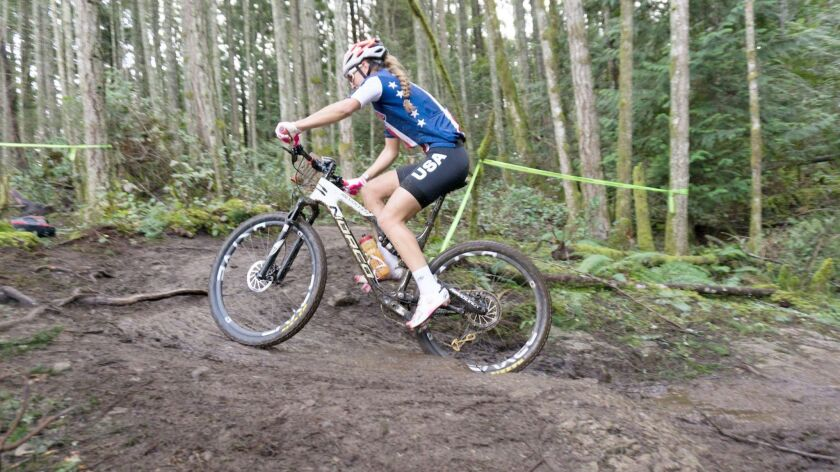Gwendalyn Gibson faces obstacles such as tree roots, rocks, and even an entire tree stump along the muddy race trail.