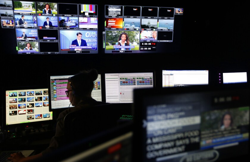 Screens show different segments for a nightly news segment in the control room at the San Diego-based One America News
