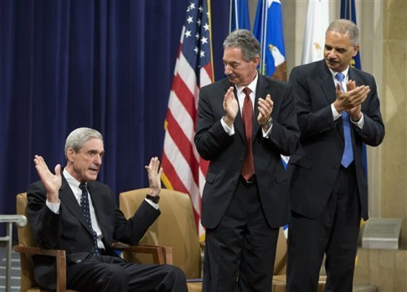 Attorney General Eric Holder, right, and Deputy Attorney General James Cole, center, applaud outgoing FBI Director Robert Mueller during a farewell ceremony at the Justice Department in Washington, Thursday, Aug. 1, 2013. Mueller is stepping down in September after 12 years heading the agency. (AP Photo/Evan Vucci)