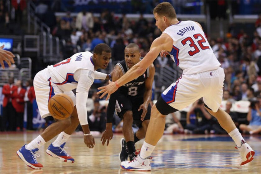 San Antonio's Patty Mills passes the ball between the Clippers' Chris Paul and Blake Griffin -- two of the NBA's highest earning pitchmen -- at Staples Center on Tuesday night.