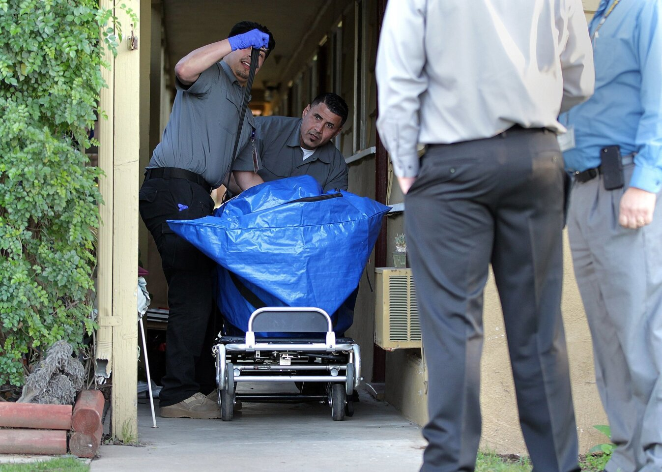 Coroner's office employees prep the gurney for transport from the home.
