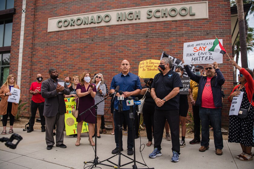 Andres Rivera, a father of an Orange Glen High School basketball player, speaks at a rally on Tuesday.