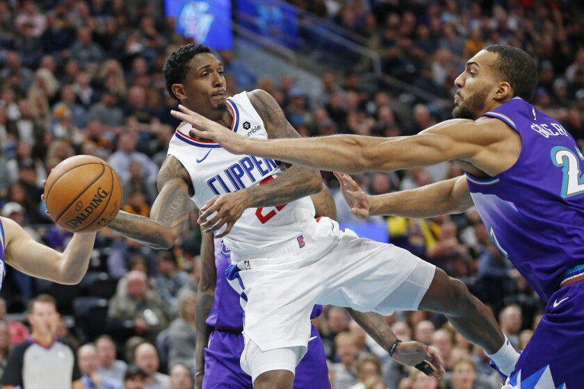 Clippers guard Lou Williams looks to pass the ball around Jazz center Rudy Gobert during a game at Vivint Smart Home Arena.