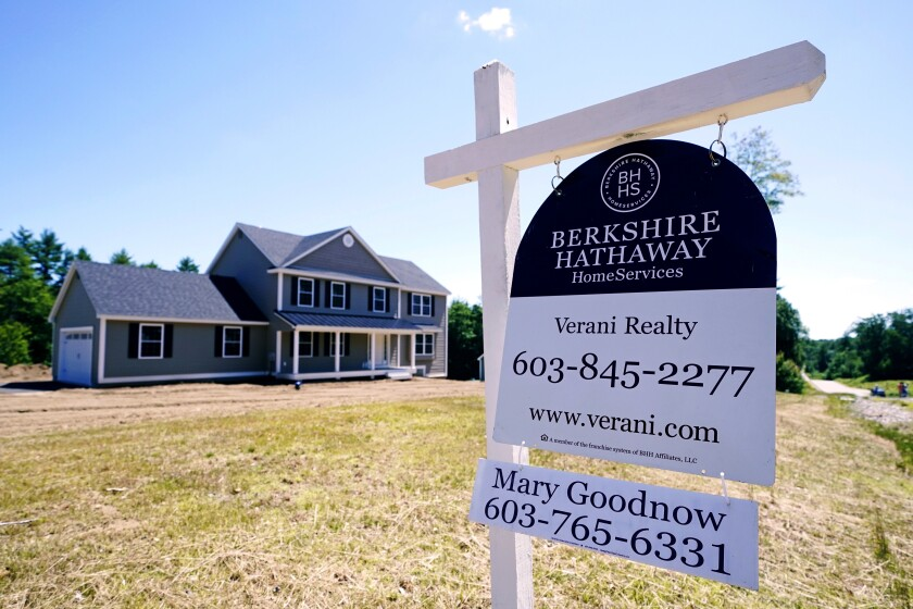A real estate sign is posted in front of a newly constructed single family home in Auburn, N.H.
