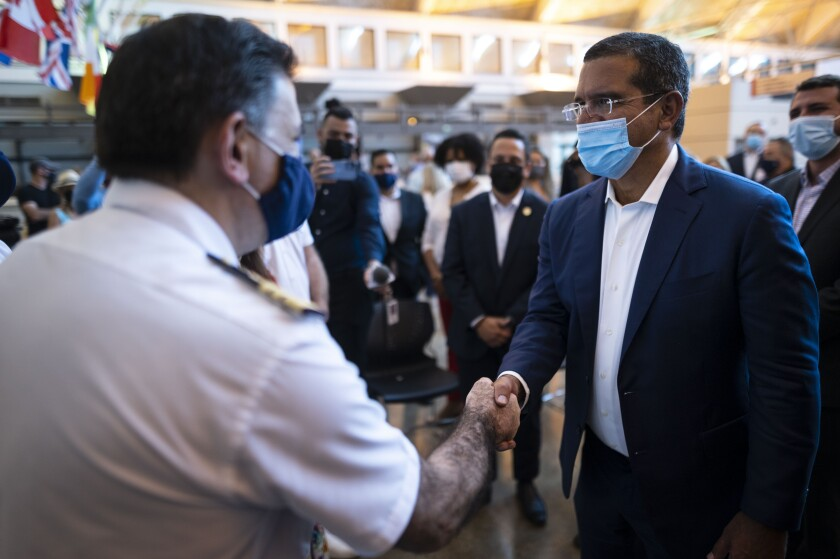 Puerto Rican Governor Pedro Pierluisi greets crew members of Carnival's Mardi Gras cruise ship, docked in the bay of San Juan, Puerto Rico, Tuesday, Aug. 3, 2021, marking the first time a cruise ship visits the U.S. territory since the COVID-19 pandemic began. (AP Photo/Carlos Giusti)