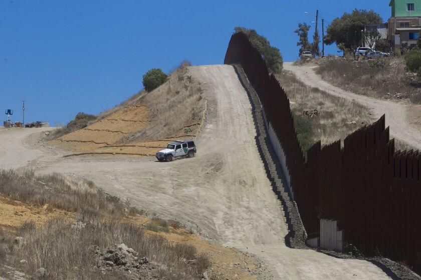 A Border Patrol vehicle patrols along a border fence.