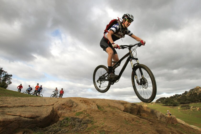 Ramona High junior Kyle Skeen gets some air off a rock during a recent after-school training ride at a rural area near the school. Skeen is coming off a sophomore season in which he won the Division II junior varsity race at the state championships in Los Olivos.