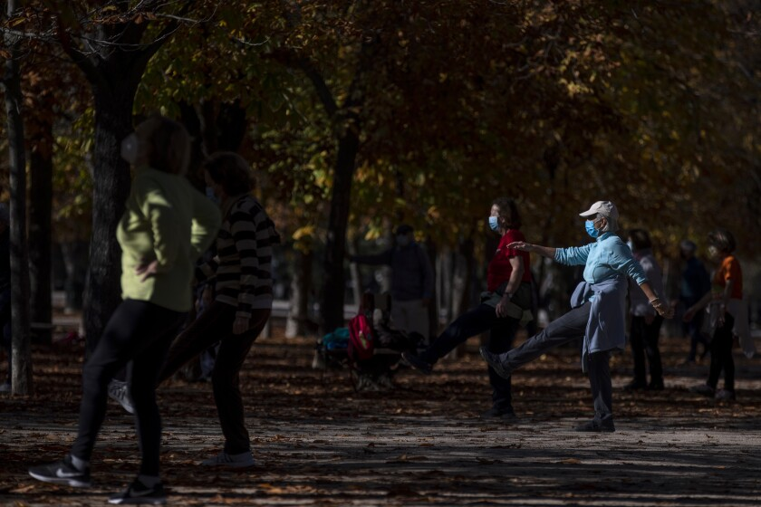 People wearing a face masks to prevent the spread of coronavirus make exercise at the Retiro park in Madrid, Spain, Thursday, Nov. 11, 2020. Spain's health ministry is reporting 411 more fatalities for the coronavirus on Tuesday, a new daily record since contagion started picking up pace this summer. (AP Photo/Manu Fernandez)